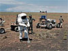 Person wearing a test spacesuit near a rover in the desert