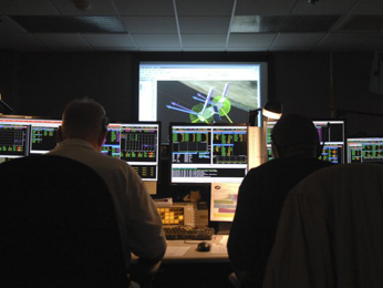 Two engineers in the Space Telescope Operations Control Center sit at consoles during the switch to Side B of the SIC and DH.