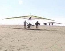 A person preparing to take off on a hang glider