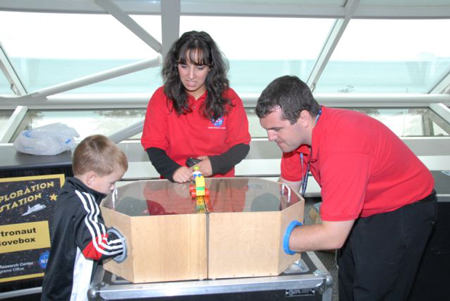 NASA Education Team assists a young visitor with the Astronaut Glove Box.
