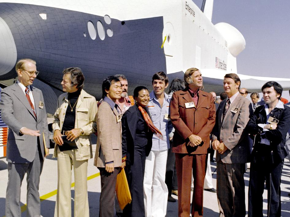 Das Space Shuttle Enterprise und die Crew des Raumschiffs Enterprise. v.l.n.r.: NASA Administrator Dr. James D. Fletcher; DeForest Kelley, Darsteller von Dr. Bones (Pille) McCoy; George Takei (Steuermann Lt. Hikaro Sulu); James Doohan (Chefingenieur Montgomery Scotty Scott); Nichelle Nichols (Lt. Uhura); Leonard Nimoy (Erster Offizier Mr. Spock); Gene Rodenberry, Schöpfer der Serie; unbekannter NASA Offizieller; und Walter Koenig (Fähnrich Pavel Chekov). Quelle: NASA