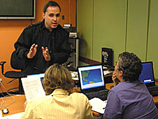 An instructor teaching two teachers at computers