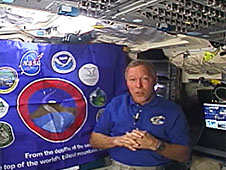 Commander Gorie floats next to a flag aboard the space shuttle