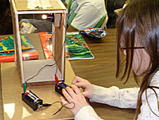 A student hooks up batteries for a chamber