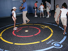 Visitors walking on a map of the solar system