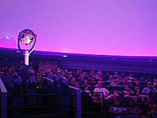 An audience seated inside the planetarium