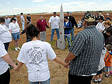 People stand in a circle with a rocket in the center