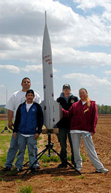 Four students stand with a rocket