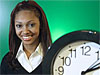 Host Alexandria Lewis stands next to a clock