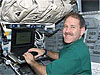 Astronaut John Grunsfeld types on a laptop computer