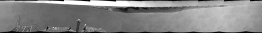 This black-and-white image shows a 360-degree panorama of 'Victoria Crater' straight ahead. To the left, Opportunity's wheel tracks extend toward the rover across the Martian plains. To the right is uncharted terrain.
