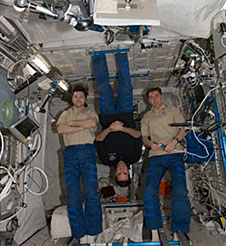 Three crew members pose on the space station, with one upside-down
