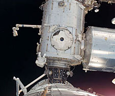 An astronaut works outside a space station module