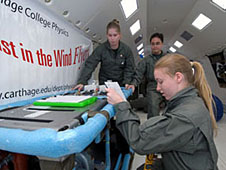 Team members working with their experiment inside an aircraft
