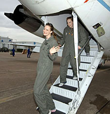 Allyson Durborow wearing a green flight suit walks down the stairs of an aircraft