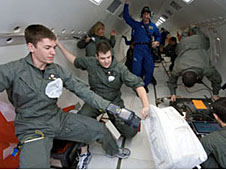 Two students working with equipment inside an aircraft