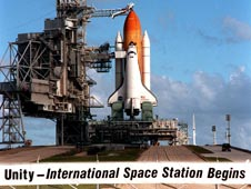 Space shuttle Endeavour on the launch pad with sign reading: Unity - International Space Station Begins.