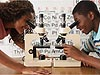 Two students smile as they look into microscopes