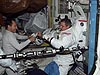A Cosmonaut helping an astronaut put on a U.S. spacesuit