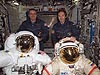 Crew members on board the International Space Station stand behind two spacesuits