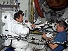 An Astronaut helping a cosmonaut put on a U.S. spacesuit