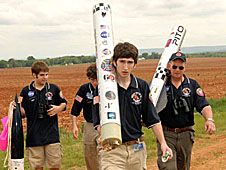 Team members holding large sections of a rocket