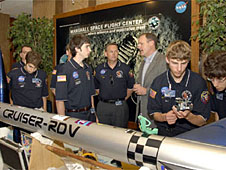 Rocket team members and Jim Halsell standing beside a rocket laid on its side