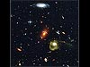 A jumble of galaxies including a yellow spiral galaxy, a young blue galaxy and several smaller red galaxies