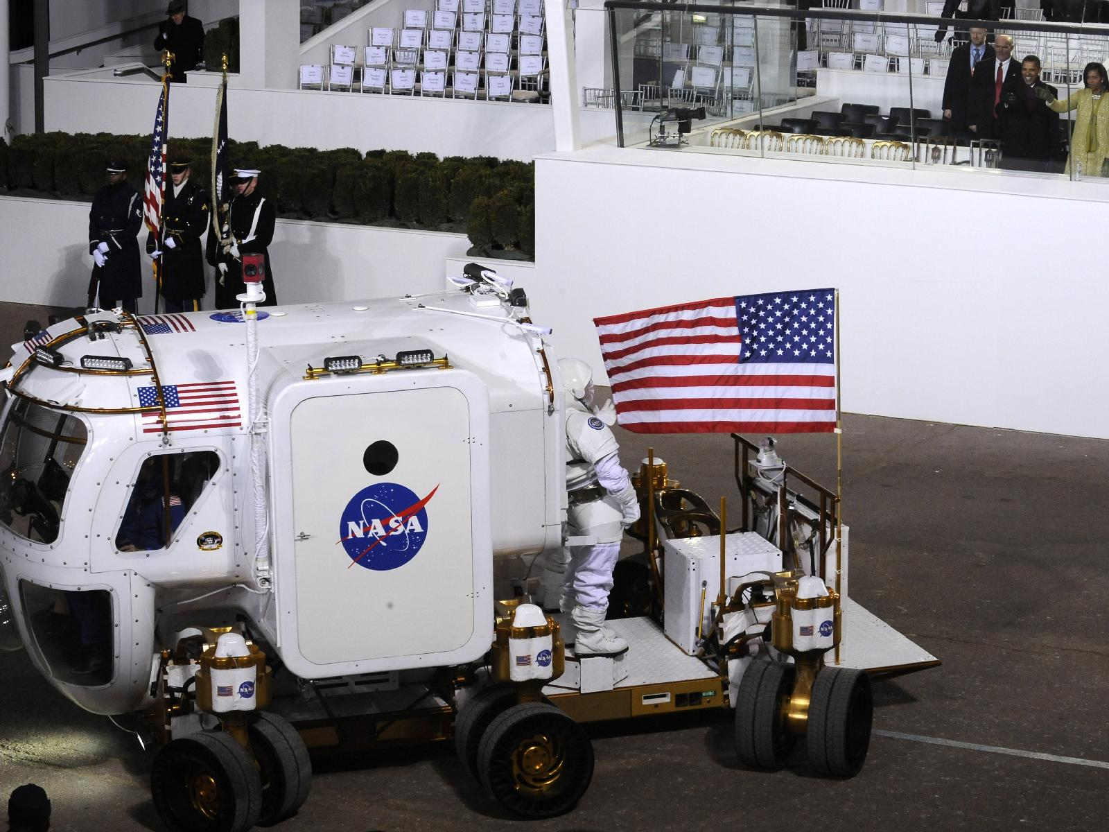 President Barack Obama, Michelle Obama and Vice President Joe Biden watch as the NASA Lunar Electric Rover stops in front of the Presidential reviewing stand on Pennsylvania Avenue in front of the White House in Washington, Tuesday, Jan. 20, 2009.