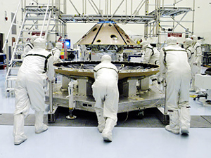 During pre-launch processing, workers move the MER-1 rover's heat shield toward the spacecraft's upper backshell.