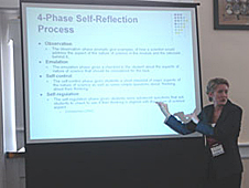 Erin Peters pointing to a projection screen during a presentation
