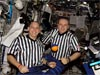 Astronaut Clayton Anderson and cosmonaut Oleg Kotov wearing referee shirts pose with a small basketball