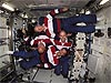 The STS-105 crew poses sideways and upside down in an empty Destiny lab of the space station