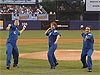 Three astronauts near the pitcher's mound in New York's Shea Stadium throw out the ceremonial first pitch
