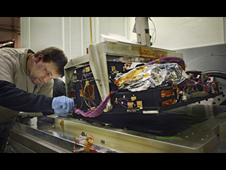 Technician Andrew Scharmann prepares the replacement SI C&DH for vibration testing at a Goddard Space Flight Center vibration laboratory.