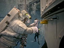 Spacewalking astronaut Michael Good uses an underwater version of the Pistol Grip Tool during this week's NBL activity to practice opening Hubble's aft shroud doors.
