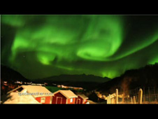green aurora over houses
