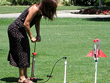 A woman using an air pump to launch a 2-liter bottle rocket