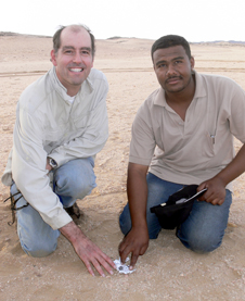 Left to right: Peter Jenniskens, meteor astronomer at NASA Ames Research Center, Moffett Field, Calif., and the SETI Institute Mountain View, Calif., and Mohammed Alameen, a student at the University of Khartoum, Sudan, point to the first meteorite from asteroid 2008TC3 found.