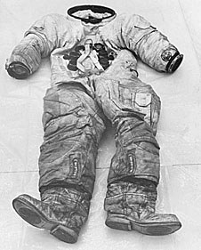 A black and white image of a spacesuit lying on a table