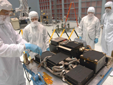 Technicians prepare the replacement SI C&DH for testing in a large clean room at the Goddard Space Flight Center.