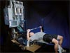 Man lying on an exercise bench uses his arms to extend equipment rod upward