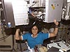 Sunita Williams holds a treadmill above her head inside the space station