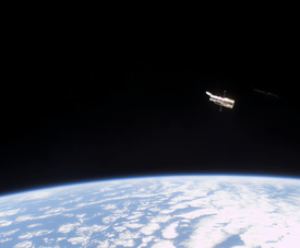Hubble orbiting above Earth with the blackness of space behind