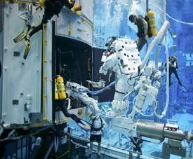 Divers training with astronauts on the mock-up of NASA's Hubble Space Telescope