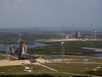 Space shuttle Atlantis and Endeavour on the launch pads as seen from the air.