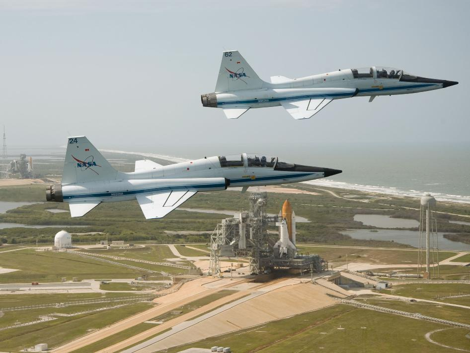 NASA pilots Jack Nickel and Charles Justiz flyover the shuttles on the launch pad.