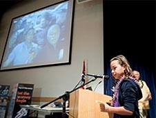 A student asking a question into a microphone and a video image of astronauts on the wall in front of her