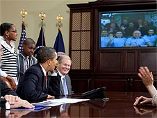 President Obama talking on a phone and looking at astronauts on a TV screen