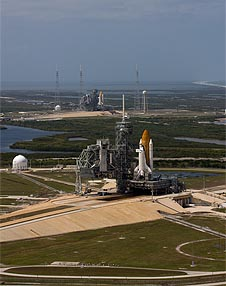 One shuttle is visible on a launch pad in the foreground; another is in the background